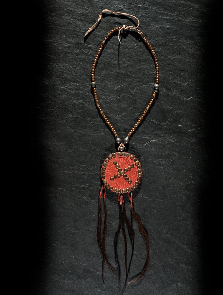 Northern Plains Tacked Hide Amulet Necklace From the Collection of Marvin L. Lince, Oregon 4/4/2014 - American Indian Art: Live Salesroom Auction thick buffalo hide disk ornamented in 63 brass tacks and coated with red pigment is attached to a hide thong strung with brass beads and 55 caliber lead shot; six strands of hair with sinew wrapping hands from lower portion of disk; TR 55 inked on reverse, diameter of disk 4 in.; overall length 25 in. 19th century