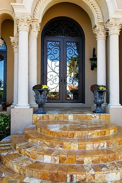 Wrought Iron entry door by Cantera Doors.  Love the door, the columns, the steps, and the urns....it all!!