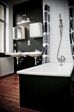 This shows that a black and white deco inspired bathroom can work with timber floor....