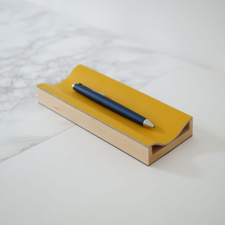 A brightly coloured reclaimed leather and sustainably sourced beech wood is used in a unique way to create this simple, contemporary desk accessory and pen tray handmade in Norfolk. Use it to store pens or any loose items and keep a limited desk area tidy. It has a rubberised base to help it grip to the desk surface or wherever you may want to display it.Each piece is handmade and finished in Danish oil Colour: Yellow or Blue Material: Beech Wood and Reclaimed Leather Dimensions: H2.5cm x…
