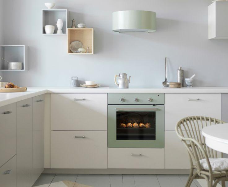 Grijsgroene afzuigkap en oven in een witte keuken met witte werkbladen en roestvrijstalen handgrepen