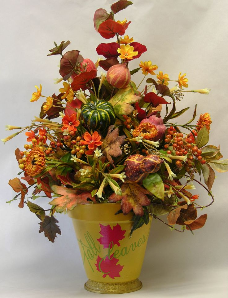 Your fall decor will be complete with this arrangement filled with so much color of the season. Eucalyptus stems, honeysuckle vines, gourds, sunflowers, pumpkins, berries and leaves in a golden clay c