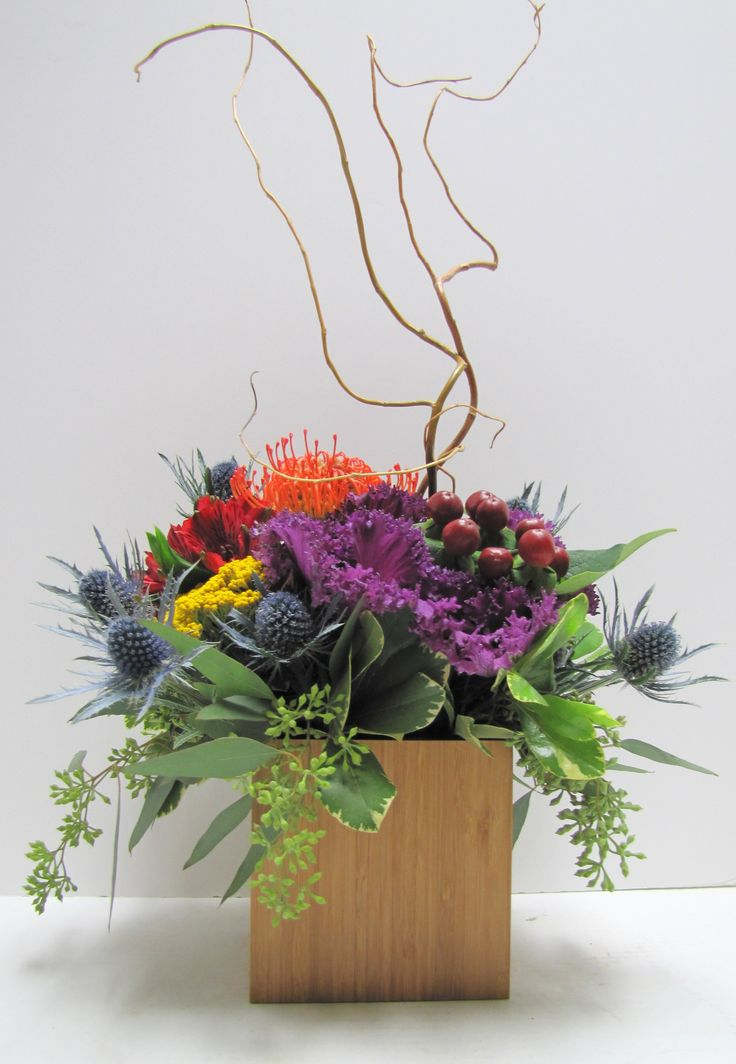 Ornamental Kale, Thistle, Seeded Eucalyptus, and a Protea blossom with a touch of curly willow in this unique arrangement.