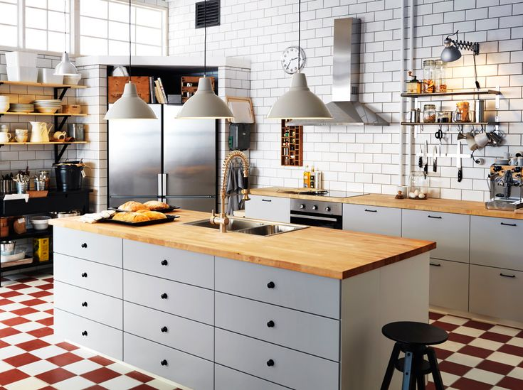 Large white IKEA family kitchen with island, wooden worktops and stainless steel appliances