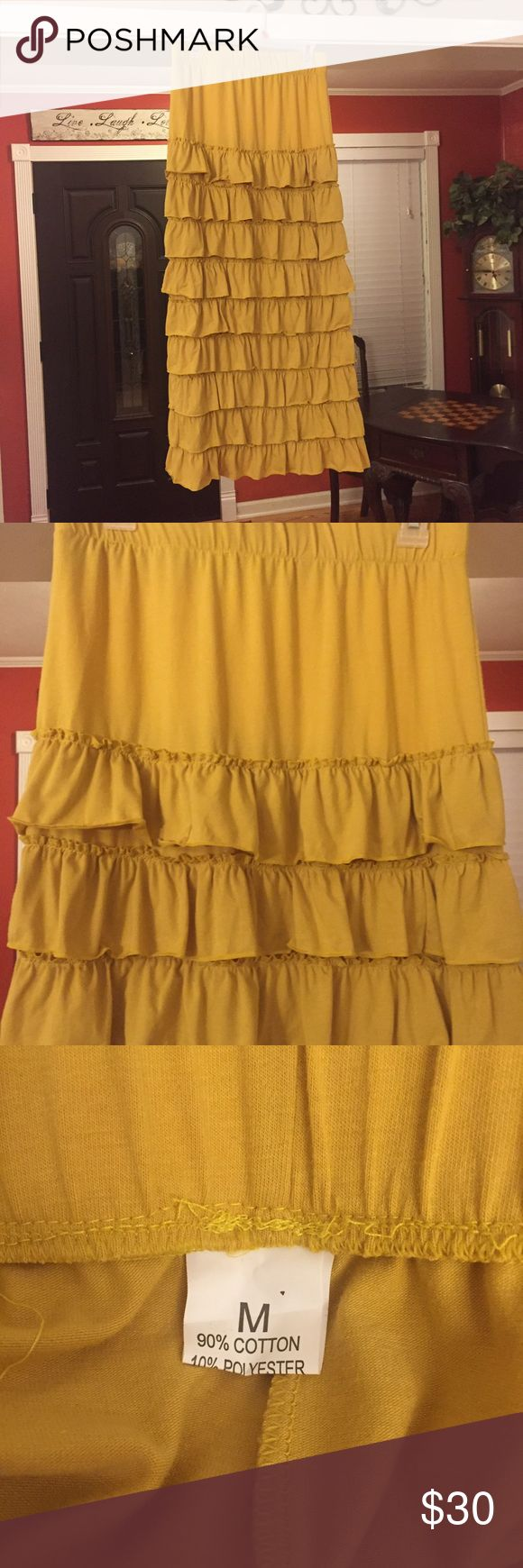 """NWOT Mustard Yellow Layered Ruffle Skirt medium NWOT Mustard Yellow Layered Ruffle Skirt Size Medium. ***Has a tiny hole in the top and the side of the top side looks like the ruffle was taken off. Not noticeable if a top is worn down to the ruffle part. It was that way when I got it in.*** Skirt is 39"""" long and waist is 15"""" flat but stretches. 90% cotton Skirts"""