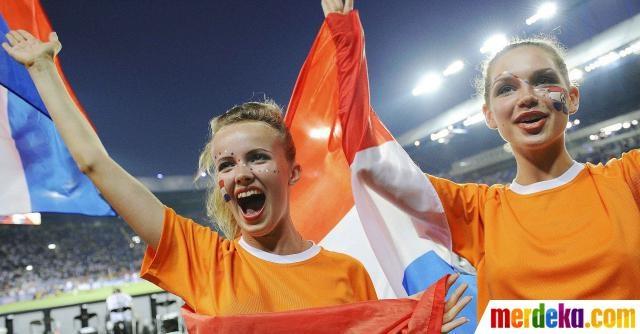 Dua suporter membawa bendera Belanda bersorak saat akan digelar pertandingan Belanda melawan Jerman.