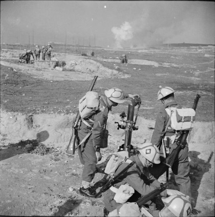 THE BRITISH ARMY ON MALTA 1942. A 3-inch mortar team laying a smoke screen during a demonstration exercise, 13 April 1942. Note helmet camouflage.