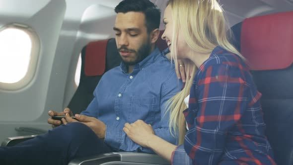 On a plane Beautiful Young Blonde with Handsome Hispanic Male Watch Videos on Smartphone