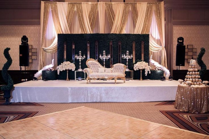 #ArtDeco inspired #reception stage with boxwood panels graced with slim mirrors, #champagne, offwhite and #goldsequin draping to add some #drama. #crystal #candelabras, oversized white #freshfloral arrangements and our elegant #whitepeacock Thank you @rumenovphotography for the beautiful image!
