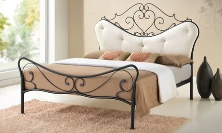 Romantic, antique-inspired wrought iron bed frame outfitted with modern comfort in the form of an upholstered headboard