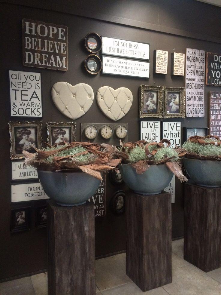 Prachtige grijze potten op houten zuilen bij intratuin