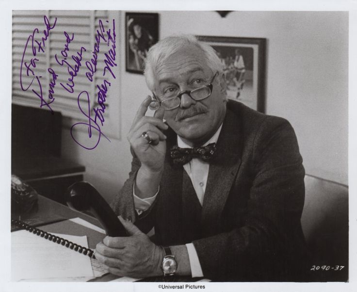 MARTIN STROTHER: (1919-1980) American Character Actor, famous for his roles in Westerns alongside John Wayne as well as for his role in Cool Hand Luke opposite Paul Newman. Signed and inscribed 10 x 8 photograph of Martin in costume as Joe McGrath, seated in a half length pose behind a desk in a scene from the film Slap Shot (1977) which also starred Paul Newman. Signed in bold purple ink across a clear area of the image. Scarce.