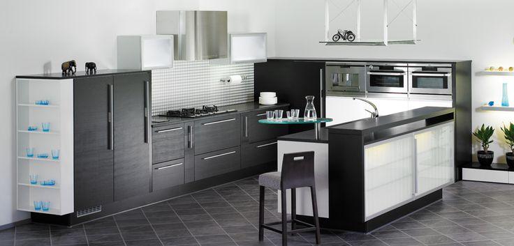 Матовая обработанная щеткой каменная плита является самой популярной новинкой кухонного дизайна. Результат, в сочетании с дверями из поперечно-шлифованного соснового шпона и легкими дверями из стекла «мороз», поражает вневременной непринужденной элегантностью. Стеклянный шкаф-руло с подсветкой и настенные шкафы со светильниками в дне подчеркивают изысканную атмосферу шелковистым светом. Товары на иллюстрации: