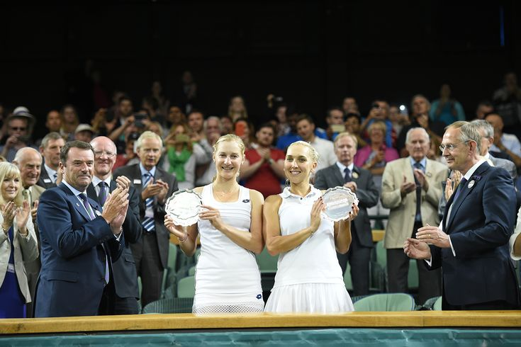 Ekaterina Makarova and Elena Vesnina hold up the ladies' doubles runners-up trophies on Centre Court