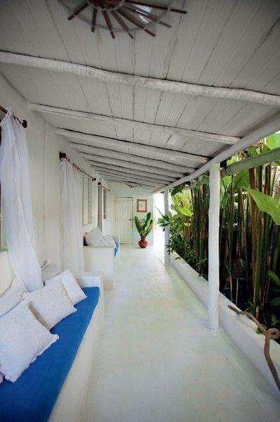 Varanda | Na área, os sofás de alvenaria, o teto e o piso foram pintados de branco. As cortinas e as almofadas de algodão foram feitas por Nelly. O colorido fica por conta do verde das bananeiras (Foto: Marco Antonio)