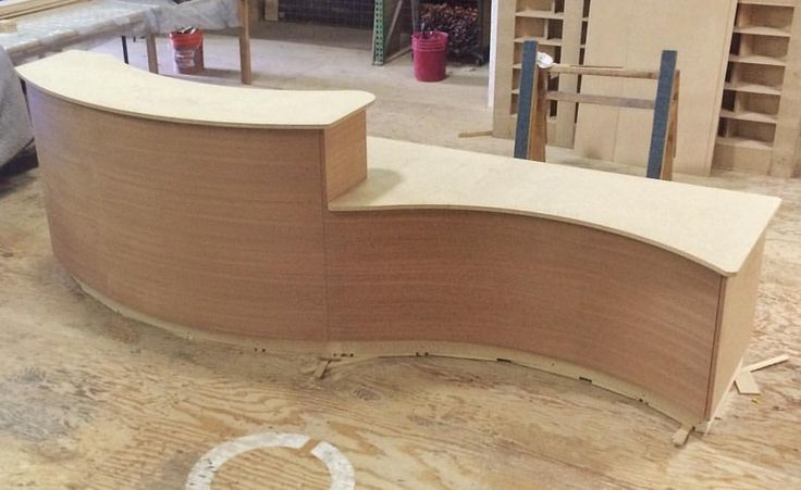 Curved reception desk ready for finish.  Sapele on the front and finished ends.  Special hidden routing for the LED lighting system is behind the panels.
