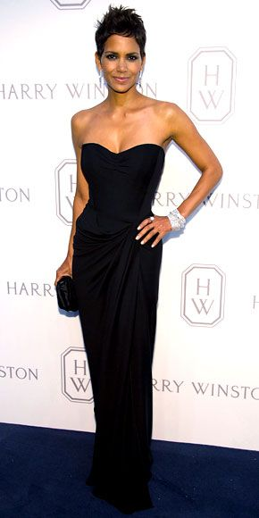 Halle Berry  WHAT SHE WORE  Berry attended the Harry Winston Court of Jewels Recreation Launch in a sleek black Dolce & Gabbana gown and embroidered half bow duchess satin Marchesa clutch.