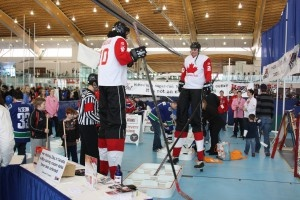 Men on stilts playing HBOX hockey at HOCKEY DAY IN CANADA