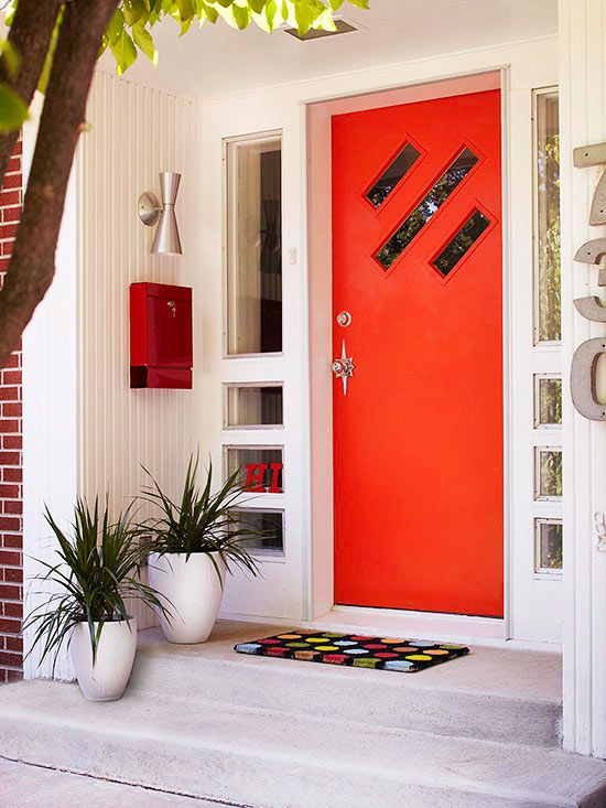 Sometimes a large front door painted a bright color can feel static and visually unappealing. In that case, it's helpful to add relief for the eye as well as for the design. Here, the homeowners opted for a plain door broken up by a trio of angled windows, as well as matching sidelights with a series of narrow and small panes. Complements to the contemporary style of the door include the unusual sconce and fire-engine red mailbox.