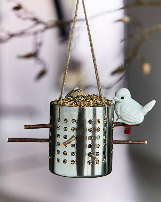 An IKEA ORDNING utensil holder is filled with bird seed and hung to be used as a bird feeder.