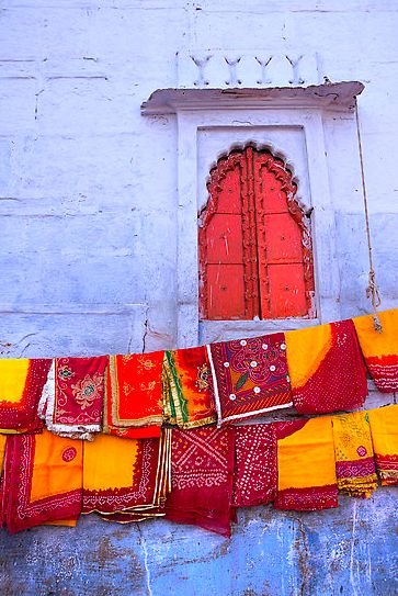 Beautiful textiles stand out even more against the textural white exterior of the building. Also love the cherry red pop of the door.