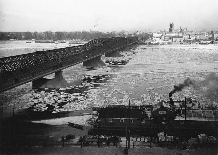 Most Kierbedzia, widok na Pragę. Cumujące przy brzegu statki żeglugi rzecznej podczas załadunku. fot. 1936r., źr. Narodowe Archiwum Cyfrowe.