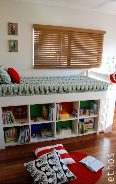 E-Decorating Before and After Photos by Ethos Design. A young boy's bedroom with a Dr Suess influence. White loft bed with cubby underneath and built in bookshelves with DIY art, tree wall decal and red circle rugs. The room has a colour scheme of red, white, yellow, blue and green