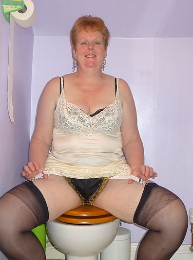 Mature lady wearing lacy vintage slip and black stockings