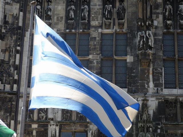 Griechische Fahne vor dem Aachener Rathaus, anlässlich der Karlspreisverleihung am 2.6.2011, bei der Griechenland zu noch härterem Sparen aufgefordert wird    (Foto: Harald Siepmann)