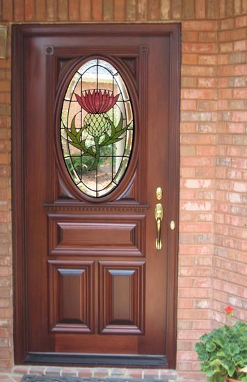 """Estate Exterior Wood Front Entry Door Style DbyD-1020. This 36"""" X 80"""" Mahogany Style A-B Door was designed, built and installed in the home of a Bagpipe Player in the St. Andrews Band in Montgomery, Alabama. After 3 trips to Scotland they decided they had to have a Thistle in their door. To make sure we did it right, we spent 3 weeks with them in Scotland and Ireland in 2007. This Leaded Beveled and Stained Glass Door is the talk of the Towne Lake Subdivision."""