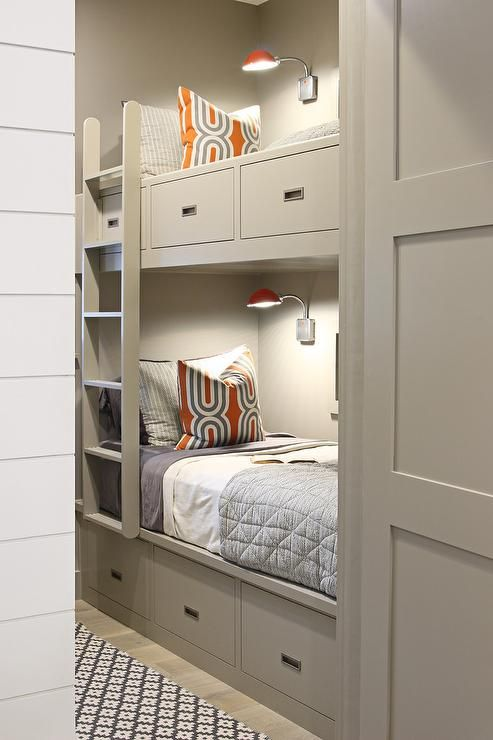Contemporary boys' bedroom features gray walls lined with gray built-in bunk beds fitted with drawers dressed in orange and gray bedding illuminated by industrial orange sconces finished with a gray ladder alongside a gray geometric rug.