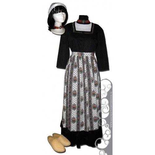 Deze klederdracht komt uit Midden-Limburg en bestaat uit een zwarte lange rok en jasje, een wit broderie blousje en een gebloemd schort. Op haar hoofd een kanten mutsje, om haar nek een ketting met grote zilverkleurige hanger en natuurlijk klompen aan haar voeten. #Limburg