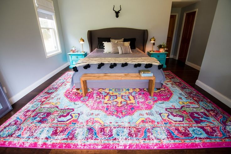 Bright modern boho style master bedroom with pink rug