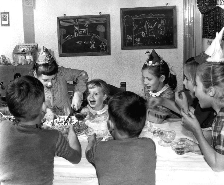 Kinderfeestje/partijtje: kinderen met feesthoedjes op zitten aan tafel te schreeuwen als de verjaardagstaart met kaarsjes wordt aangesneden door de jarige, 1963.