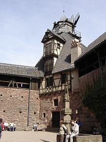 France. Château du Haut-Kœnigsbourg — La cour basse est entourée de communs et de locaux de service (écurie). Un bâtiment attenant est surmonté d'un moulin à vent. Elle comprend milieu la copie d'une fontaine du xve siècle conservée à Eguisheim, la forge et une maison alsacienne.