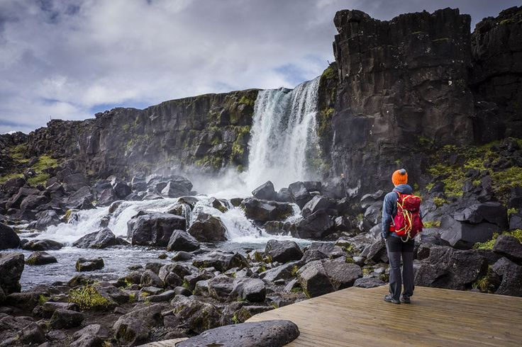 Man in outdoor clothing looking at waterfall in Iceland