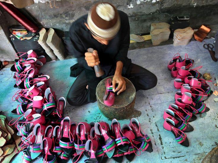 Vrijdag 26 juli: Een Indiase schoenmaker is druk bezig schoenen in elkaar te zetten in Calcutta.