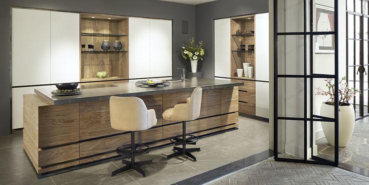 Strakke design keukens krijgen stijl en karakter door het gebruik van sprekende materialen zoals olijfhout en Canadees hardsteen.