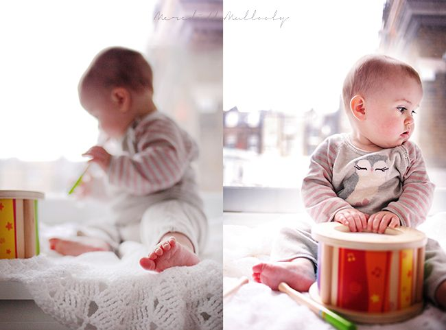This is little Eden Jean sitting in the window of her London home and she loves her toy drum.
