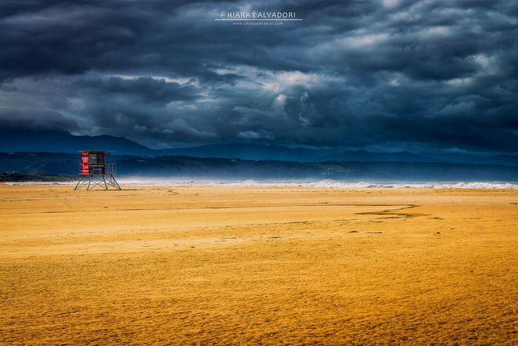Gold and Dark | I shot this picture in Plettenberg Bay, in the Western Cape region, South Africa. There was ebb tide and a thunderstorm was going away. I loved the contrast between the golden beach and the black clouds in the sky. And there, right in the middle, this red lifeguard cabin.  Western Cape - South Africa © www.chiarasalvadori.com