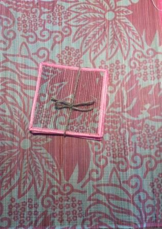 Floral print rectangle placemat with fringe and coaster in rectangle shape with ribbon edged coaster.