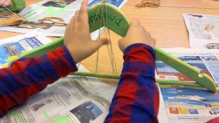 Snaarinstrument van kleerhanger en elastiekjes. Gezaagde inkepingen om elastieken op hun plaats te houden. (idee Yoni Quintens)