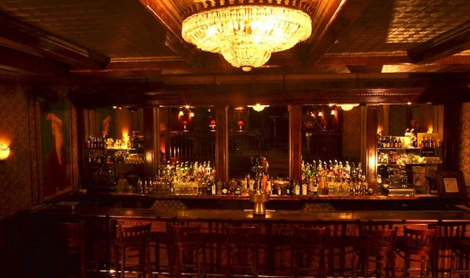The Back Room has an elegant bar with a grand chandelier overhead, the perfect atmosphere for a prohibition bar - NYC speakeasy