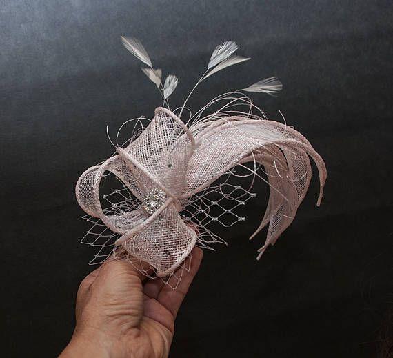 Versión de lujo para el fascinator popular. Blush rosado (nude rosado, luz rosa) fascinator hojas enrollados a mano, haciendo como una guirnalda a lo largo de la cabeza. Con adornos de pedrería pequeña en la proa y rhineston pequeño botón en el centro del arco. Plata y red blush utilizada para hacerlo más atractivo. Para el accesorio de elegir de las variaciones a su favorito: Peine (permite colocar en cualquier lugar en su tocado-mi opción favorita personal) Clip (permite colocar en…