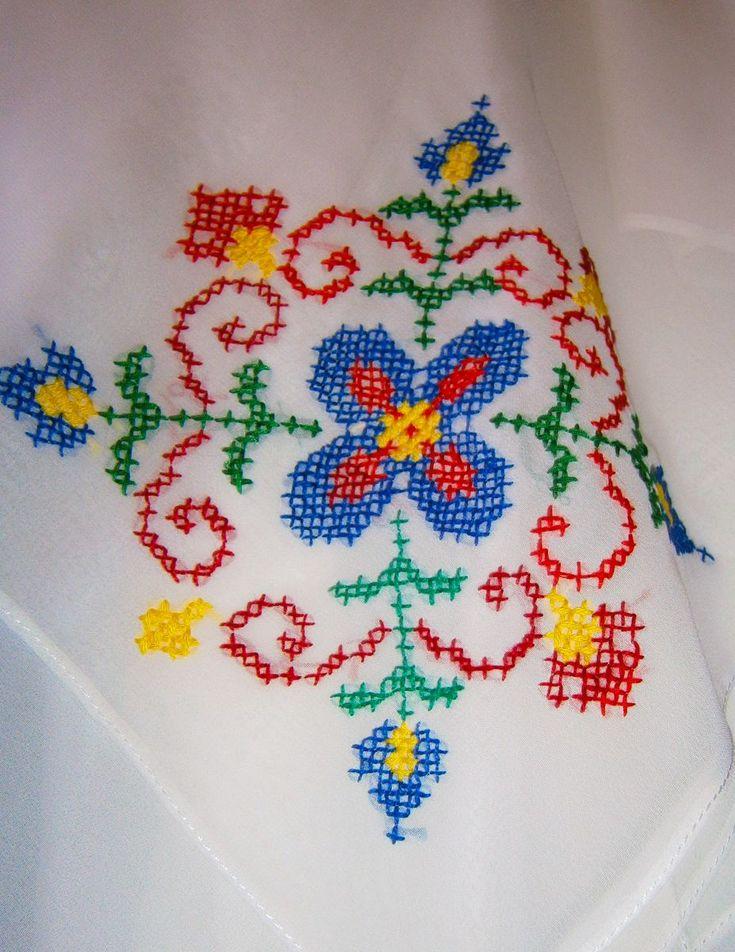 Un model de floare cusut pe o esarfa alba.