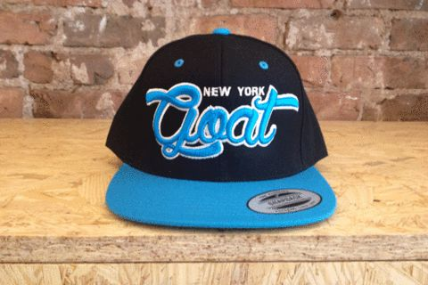 """Spiced with rock 'n' roll, this one size fits all snapback baseball cap just might be the """"greatest of all time."""" With a plastic adjustable back and substantial embroidery in a vibrant aqua, it's perfect for me & you, your mama and your cousin, too."""