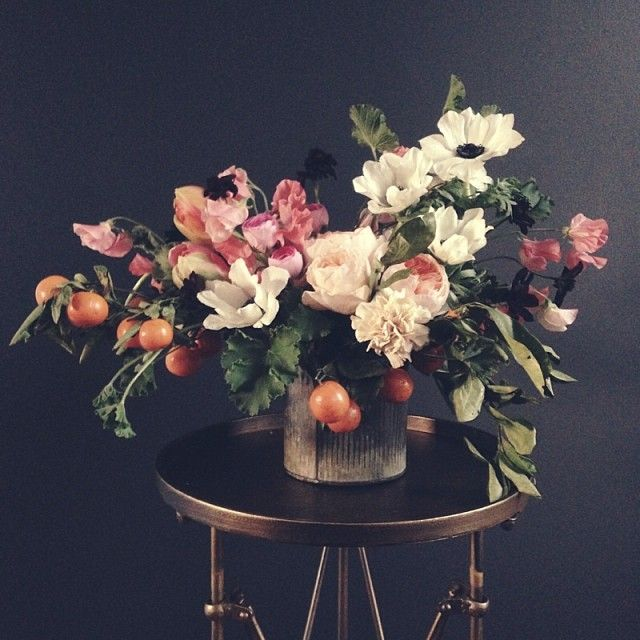 Loose, whimsical centerpiece of anemones, ranunculus, garden roses, carnations, sweet pea, chocolate cosmos, french tulips, and kumquats.