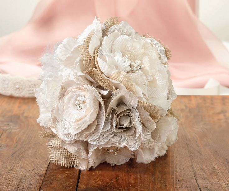 "This 7.5"" stunning bouquet encompasses rustic charm and delicate elegance. The bouquet combines burlap, shimmering rhinestones, classic pearls and ribbons into this gorgeous floral arrangement. A 4"" h"
