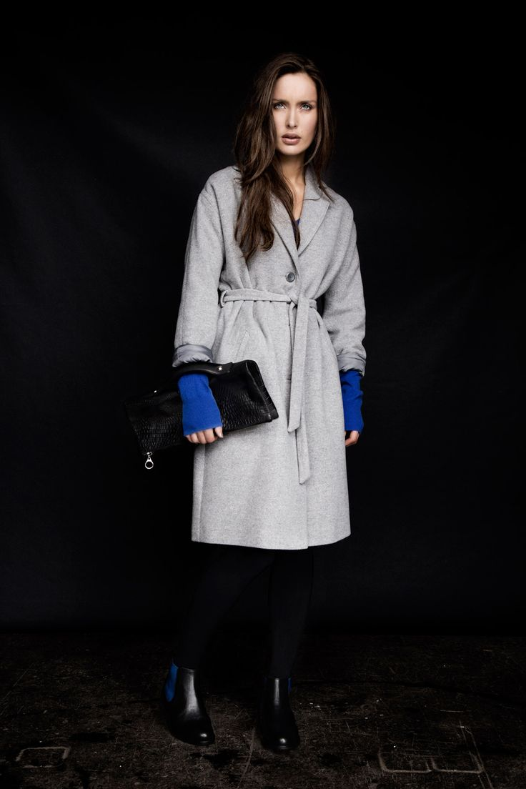 Grey belted coat, leather clutch with handle and black leather Chelsea boot with blue elasticated insert, all Carolyn Donnelly The Edit