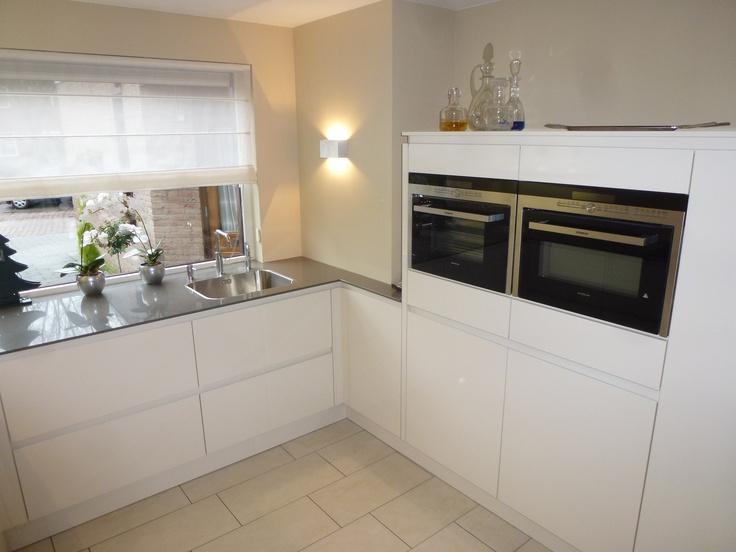 Volledig witte greeploze L-keuken met halfhoge kasten en extra dun composieten blad wat doorloopt in het raam. — in Zwijndrecht (Nederland).